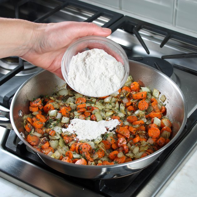 Adding flour to a saute pan with carrots and onions on stovetop