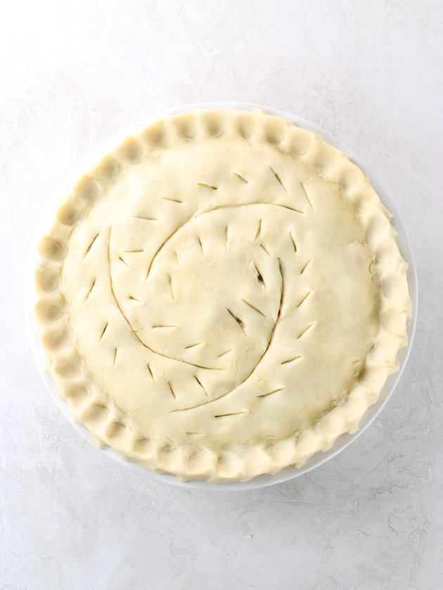 Pie with decorative scoring on top crust, before baking