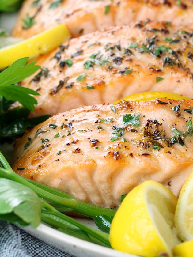 very close up eye level pieces of baked salmon on a platter with lemons and parsley
