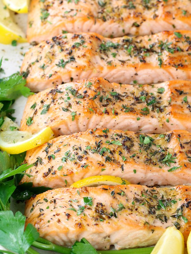 eye level close up partial platter of baked salmon filets with lemon pepper