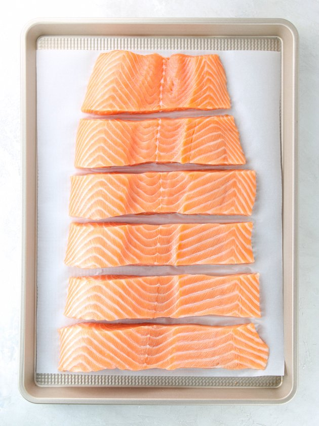 baking sheet with 6 uncooked salmon filets on parchment paper