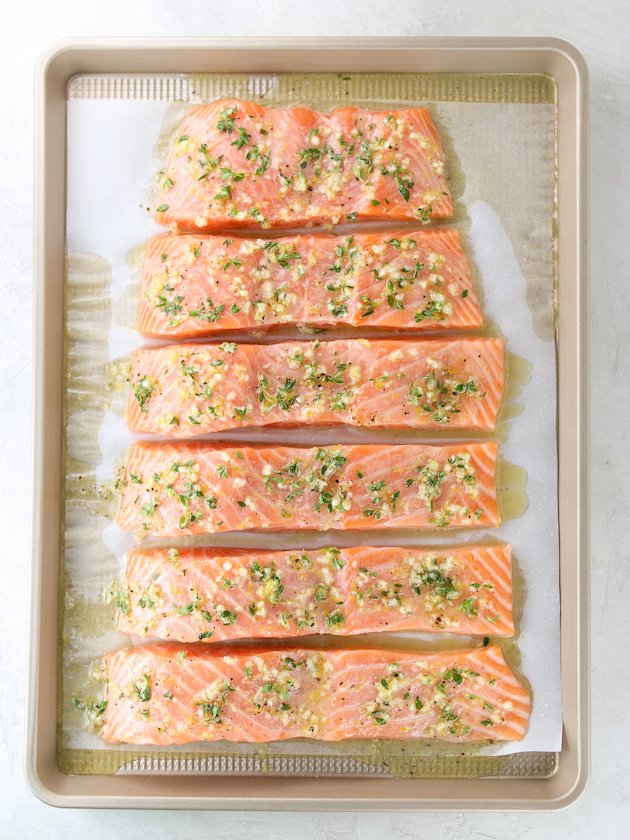 Baked Lemon Pepper Salmon with herbs and garlic on baking sheet before cooking