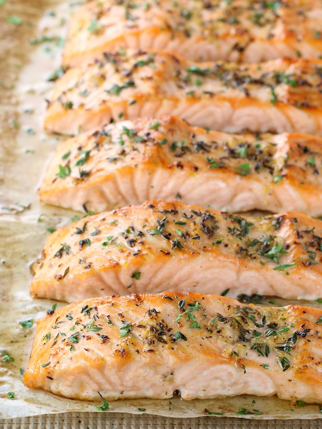 Salmon on cookie sheet with herbs
