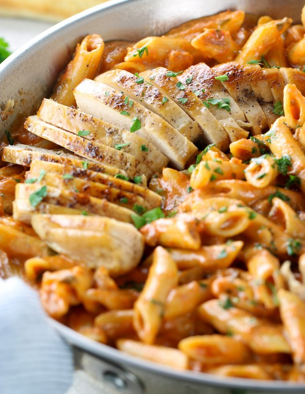 Grilled chicken sliced in partial pan of penne vodka pasta