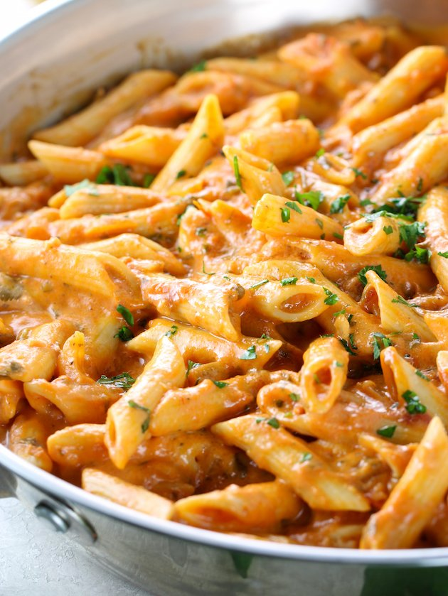 eye level close up partial pan of penne pasta with vodka sauce