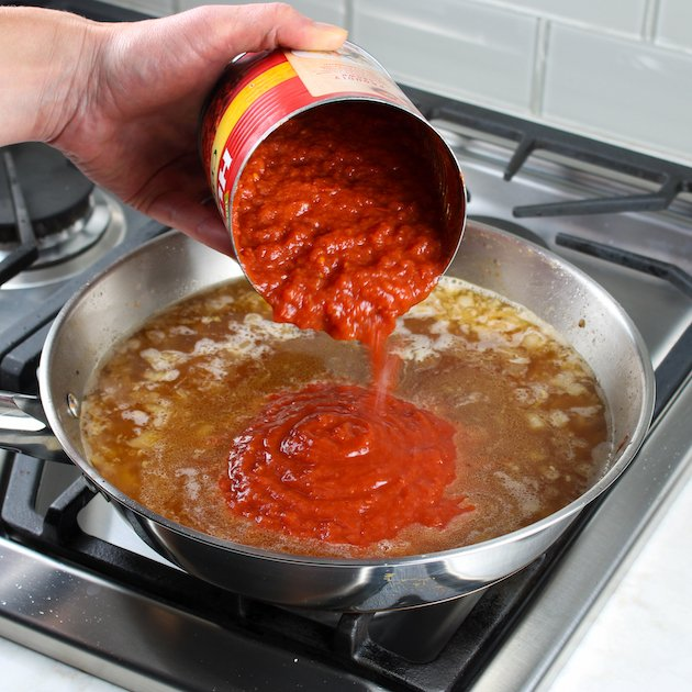 Adding tomatoes to saute pan for pasta alla vodka sauce
