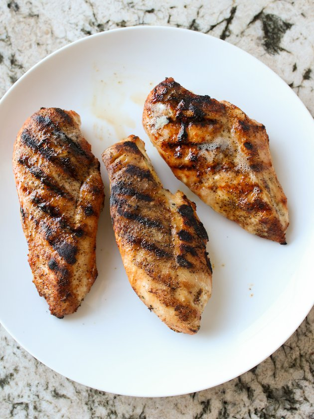 White plate of grilled chicken breasts on granite counter