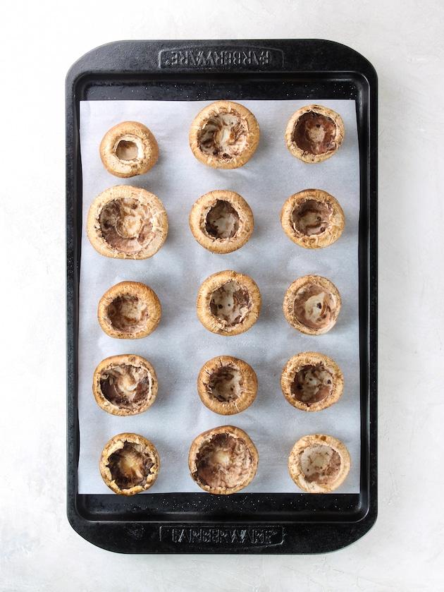 mushroom caps lined up on baking sheet before baking