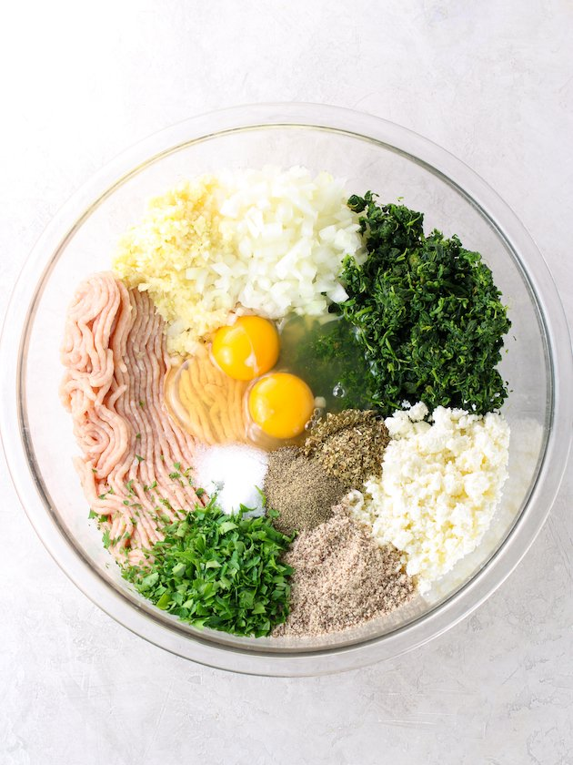 large glass mixing bowl full of ingredients for chicken meatballs