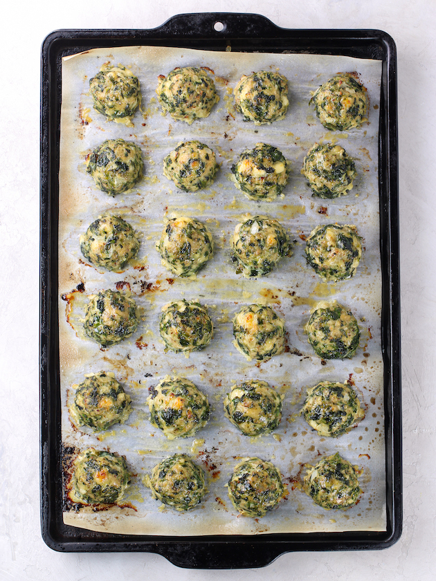 baking sheet with meatballs lined up on parchment paper after cooking