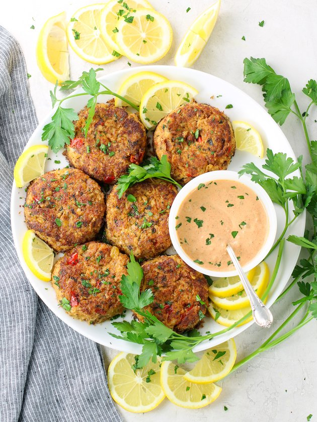 Platter of crab patties with lemon wedges and chipotle aioli