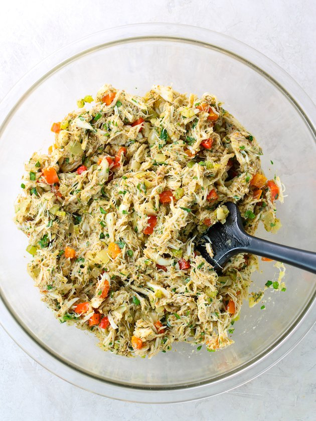crab cake ingredients mixed together in large glass bowl