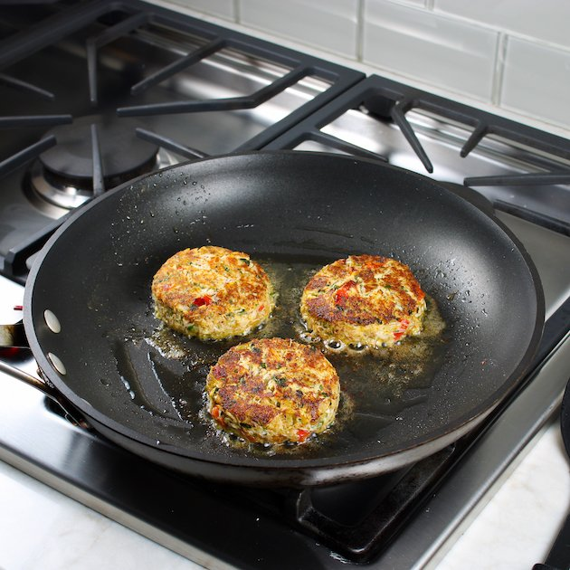 crab cakes frying in olive oil on stovetop