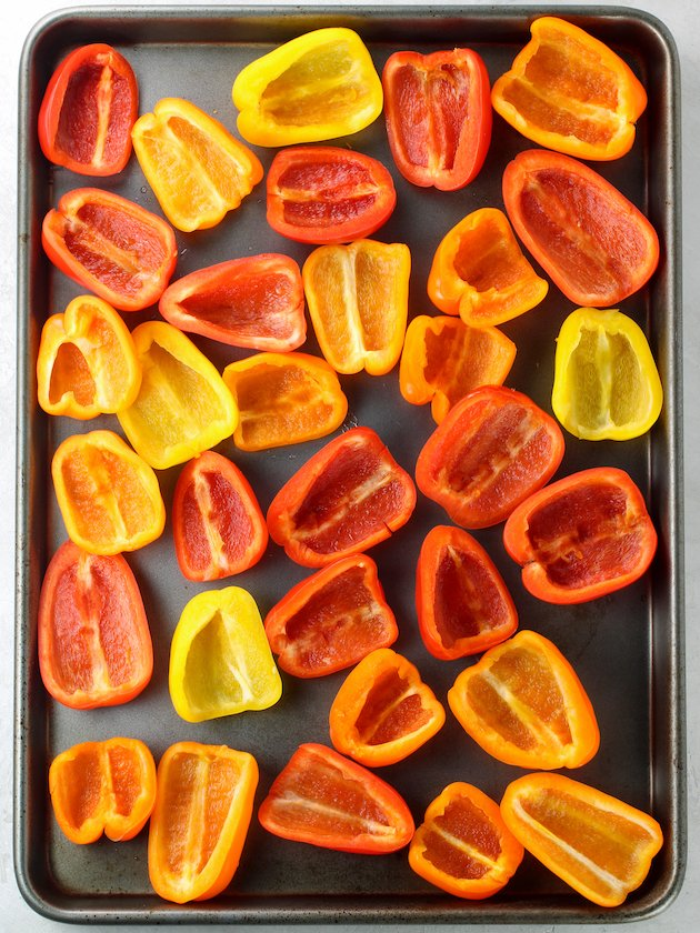 Mini bell peppers cut in half on a baking sheet