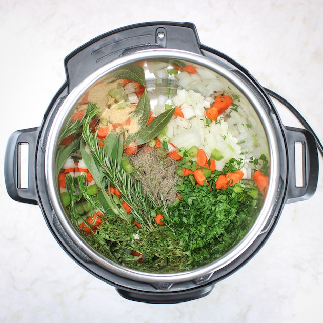 Instant pot with chopped carrots, onions, celery, herbs, and seasonings before cooking