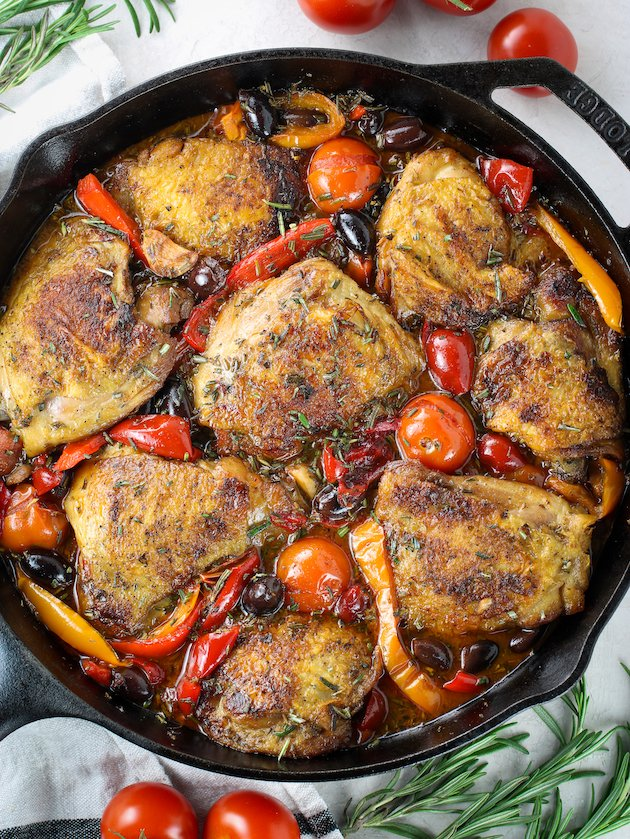 Cast Iron skillet of Italian chicken with cherry tomatoes and bell peppers