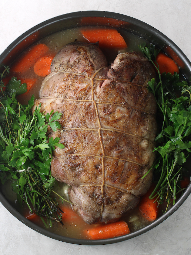 Seared and tied lamb leg in dutch oven with veggies and herbs before cooking