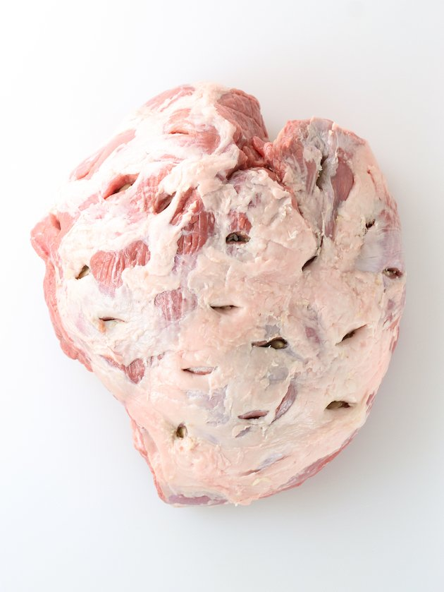 Uncooked leg of lamb with holes made for garlic cloves