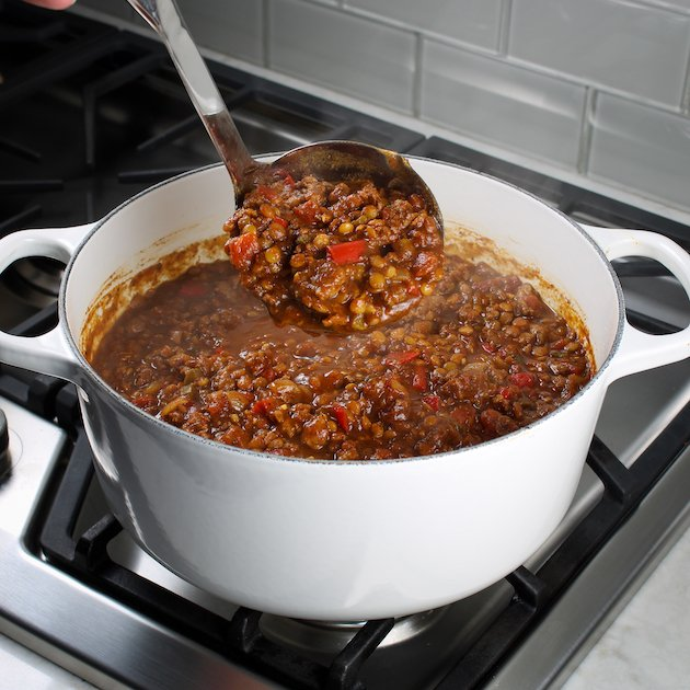 Silver ladle holding scoop of chili over a white soup pot