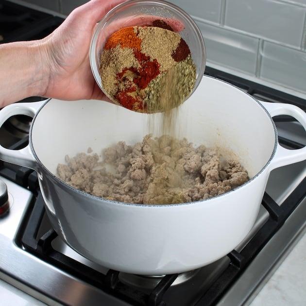 Adding seasonings to soup pot for turkey chili