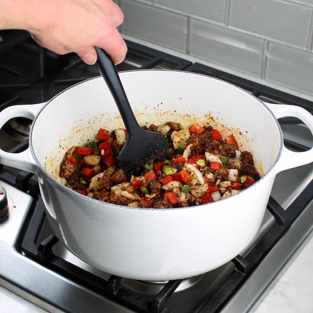 Stirring veggies into soup pot for turkey chili
