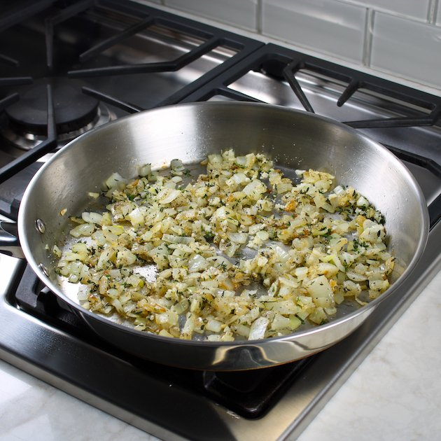 Saute pan with onions and herbs on stovetop