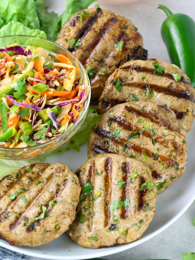 Grilled tuna burger patties on a platter with bowl of asian slaw