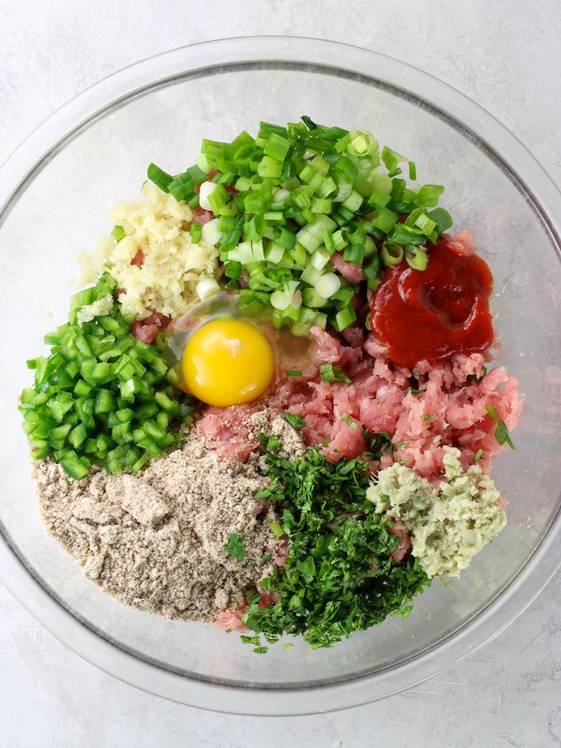 large glass bowl with burger ingredients before mixing together