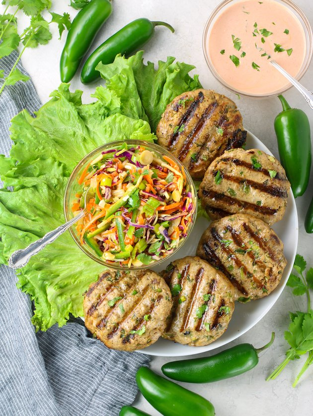 platter of grilled burgers with asian slaw and sriracha aioli