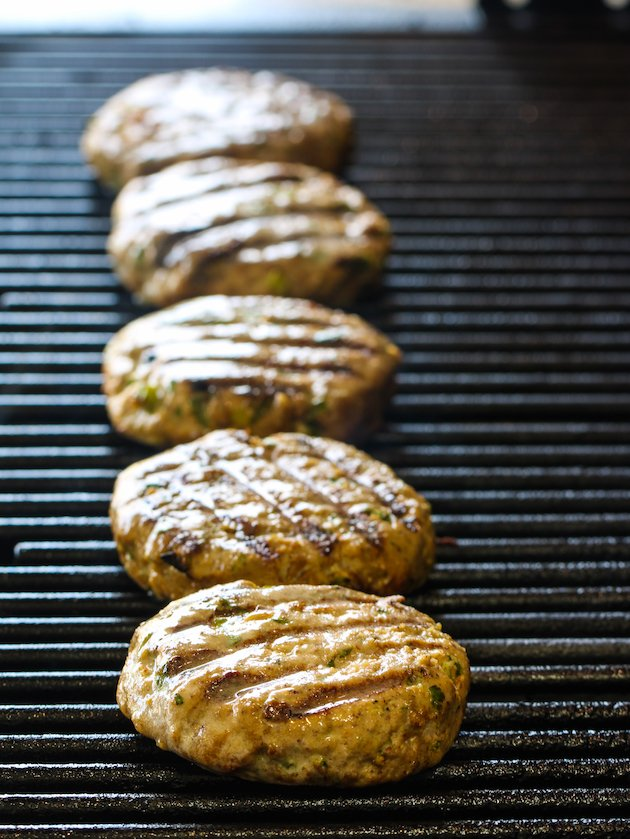 eye level 5 tuna burgers in a row grilling on hot grill