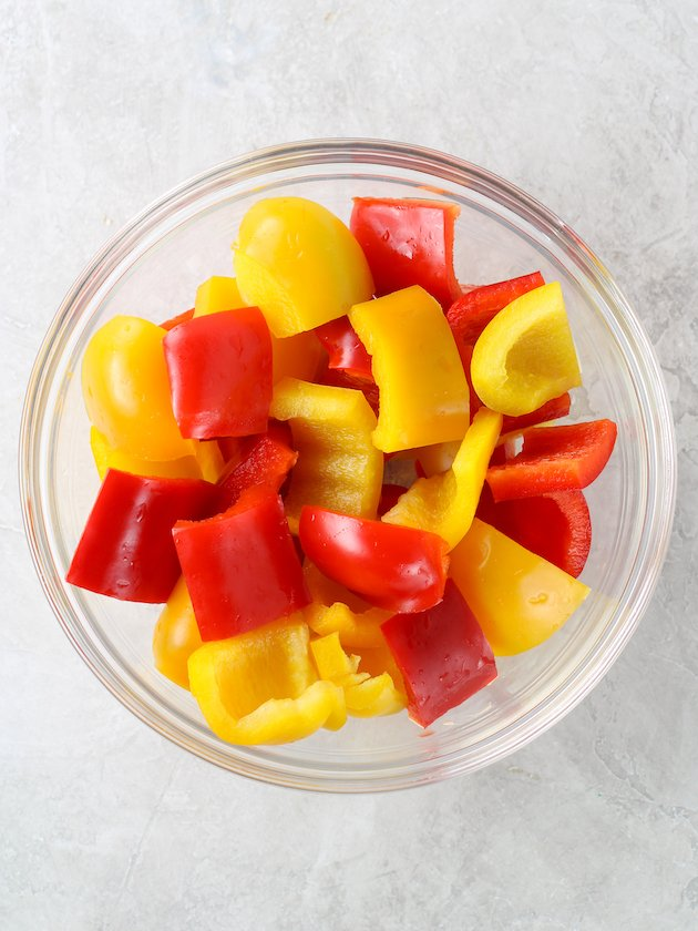 Glass bowl of chopped red and yellow bell peppers