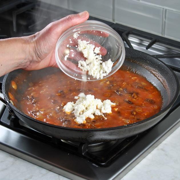 adding feta cheese to saute pan on stovetop