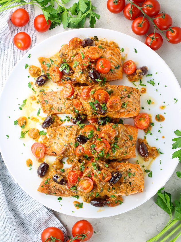 Mediterranean Salmon with Sun Dried Tomatoes and Feta on a serving dish