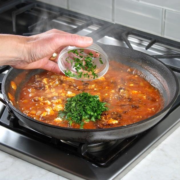 adding parsley to saute pan on stovetop