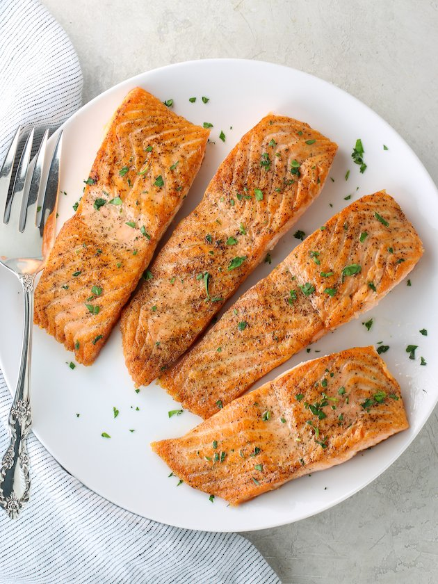 Four perfectly sauteed salmon filets on a platter with herbs