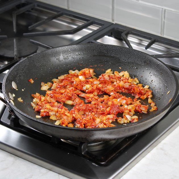 sun-dried tomatoes and onions in a saute pan