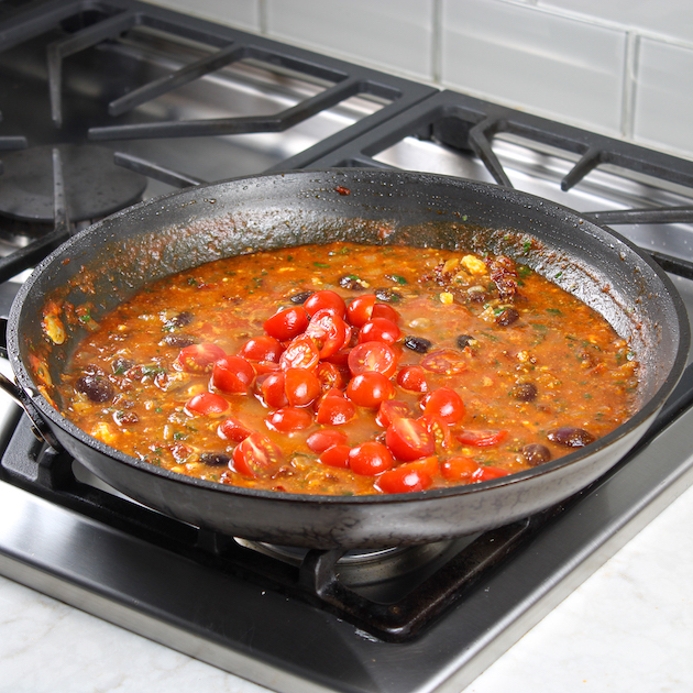 cherry tomatoes in saute pan of red sauce
