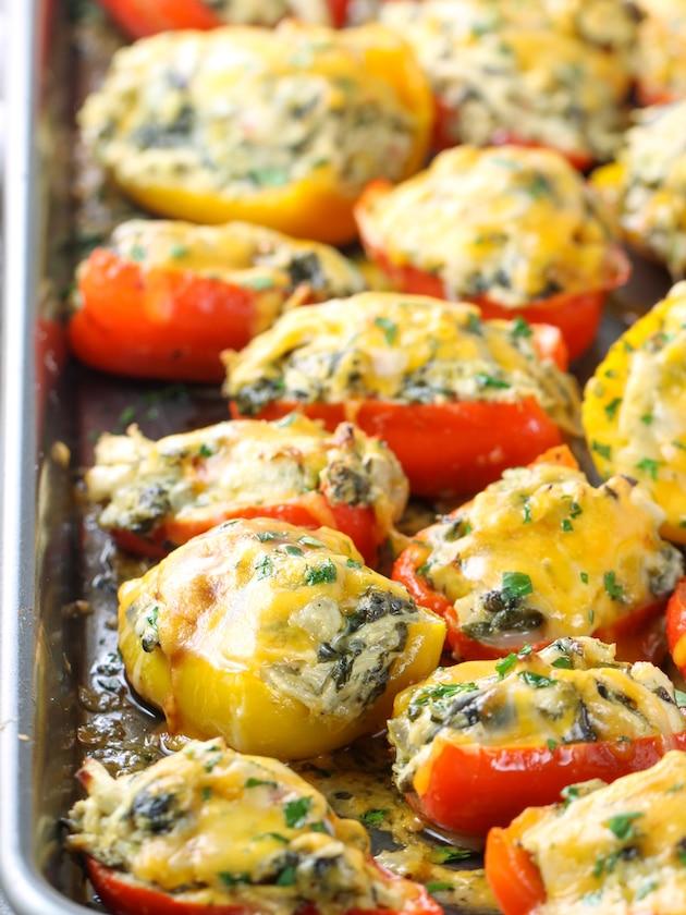 Close up eye level baking sheet of baked stuffed Chicken Artichoke Peppers