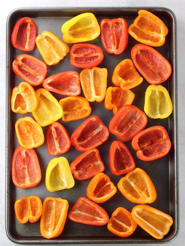 baking sheet with mini bell peppers cut in half before cooking