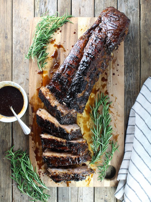 over the top wider shot of balsamic ribs on a cutting board cut up