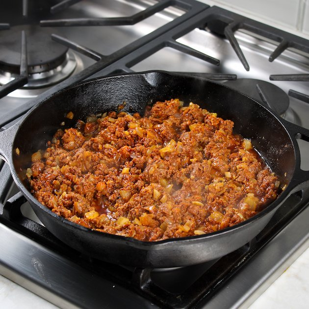 Chorizo cooking in cast iron skillet on stovetop