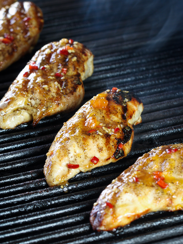 Grilling chicken breasts with peach sauce