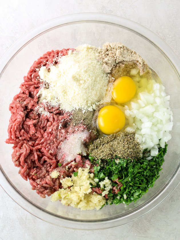 large glass mixing bowl with meatball ingredients before combining