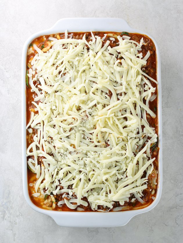 Shredded cheese on top of casserole dish full of red sauce & pasta