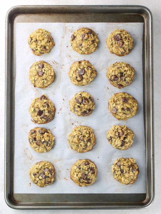 cookie sheet full of freshly baked zucchini oatmeal chocolate chip cookies on parchment paper